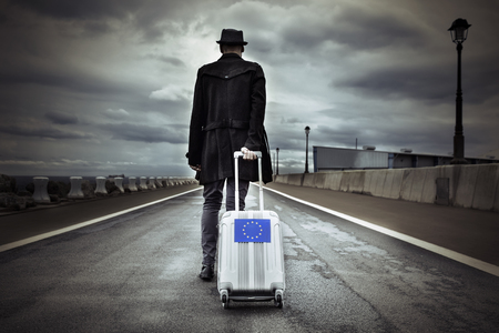 closeup of a young man seen from behind carrying his rolling suitcase with an European flag, with a dramatic effect 스톡 콘텐츠