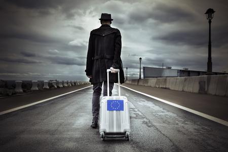 Primer plano de un joven visto desde atrás llevando su maleta con ruedas con una bandera europea, con un efecto dramático
