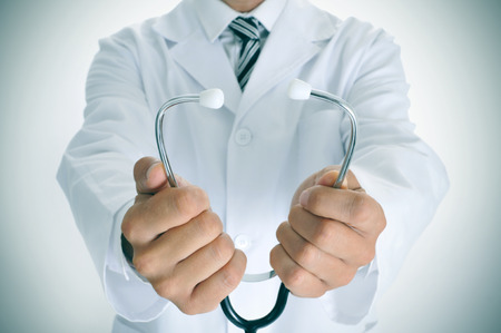 bowel disorder: closeup of a young doctor man wearing a white coat and with a stethoscope, slight vignette added