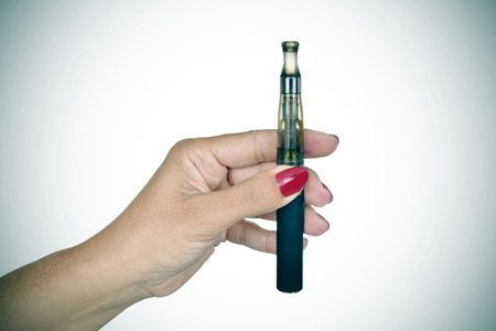 safer: closeup of the hand of a young woman showing an electronic cigarette, slight vignette added Stock Photo
