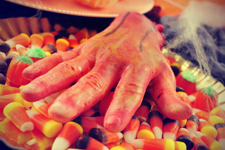 amputated: closeup of a scary amputated hand on a tray with some different Halloween candies and cobwebs, with a filter effect Stock Photo