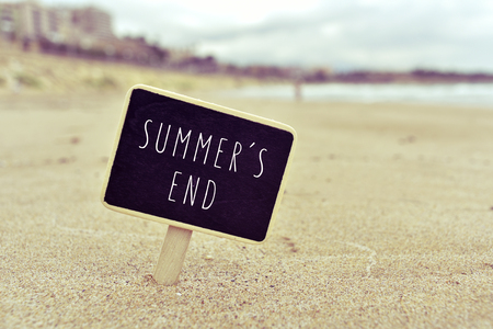 farewell: closeup of a chalkboard with the text summers end written in it, in the sand of a lonely beach