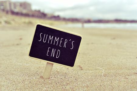the farewell: Primer plano de una pizarra con el verano termina el texto escrito en ella, en la arena de una playa solitaria
