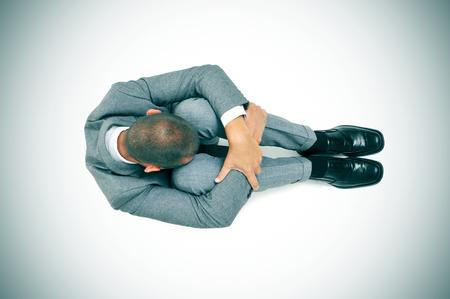 acoso laboral: un hombre de negocios acurrucada en el suelo con la cabeza entre las rodillas, ilustración leve añadió