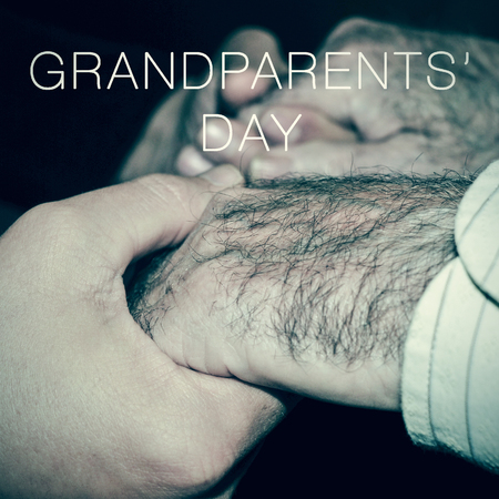 old man: closeup of the hands of a young man holding the hands of an old man, and the text grandparents day Stock Photo