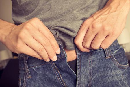 ombligo: Primer plano de un hombre joven que intenta sujetar los pantalones, a causa del aumento de peso