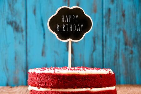auguri di compleanno: una torta di velluto rosso con una lavagna a forma di una bolla di pensiero con il testo buon compleanno, su una superficie di legno rustico blu, con un effetto retr�