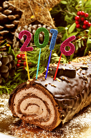yule log: a yule log cake, traditional of christmas time, with glittering numbers of different colors forming the number 2016, as the new year