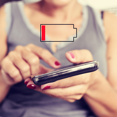 female sex: closeup of a young woman using a smartphone and an illustration of a low battery