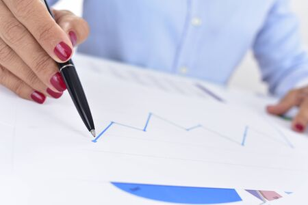observes: closeup of a businesswoman at her office desk full of graphs and charts, observes a chart with an upward trend