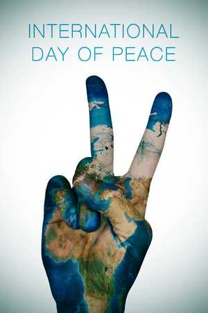 a sign: a man hand patterned with an Earth map  giving the V sign, as symbol of peace, and the sentence international day of peace