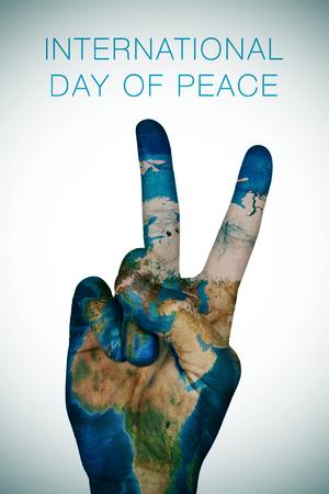 felicitaciones: una mano del hombre modelada con un mapa de la Tierra da la muestra V, como símbolo de la paz, y el día internacional de oración de la paz Foto de archivo