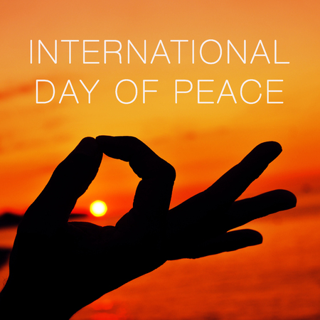 simbolo della pace: primo piano di un giovane uomo meditando con le mani in gyan mudra al tramonto e il testo giornata internazionale della pace