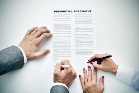 legal document: Primer plano de un hombre joven y una una joven firma de un acuerdo prenupcial Foto de archivo