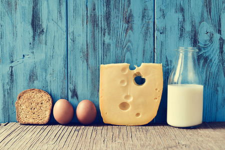 toast: a toast, some eggs, a piece of Swiss cheese and a bottle with milk on a rustic wooden table, against a blue rustic wooden background, with a filter effect
