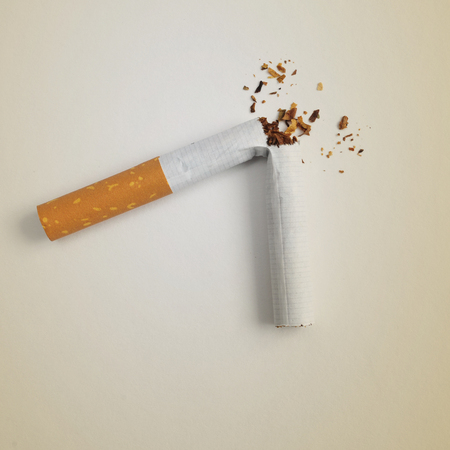 ceasing: a broken cigarette on a beige background, symbolizing quitting smoking