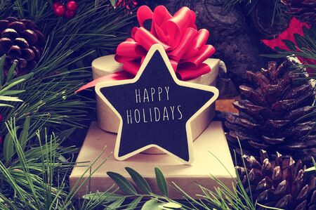 under the tree: a star-shaped chalkboard with the text happy holidays on a pile of gift boxes placed under the christmas tree and surrounded by natural ornaments such as pine cones Stock Photo
