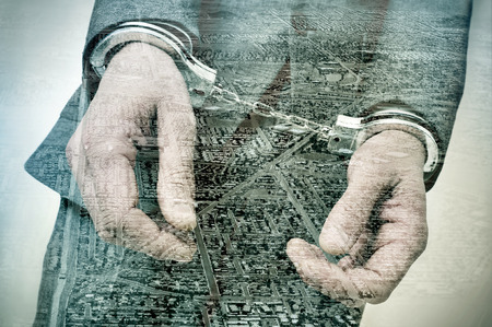 justicia: doble exposición de un hombre esposado y una urbanización vías y terrenos en desarrollo, que simboliza el delito de especulación inmobiliaria Foto de archivo