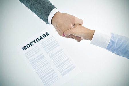 lend a hand: closeup of a young man and a young woman shaking hands above a table with a mortgage loan document, slight vignette added