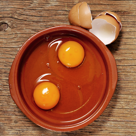 yesteryear: high-angle shot of an earthenware plate with some cracked chicken eggs on a rustic wooden table