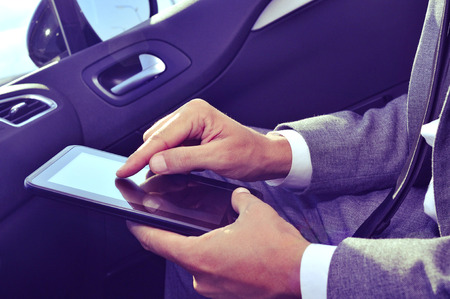 closeup of a young caucasian businessman in suit using a tablet computer in a car Stock Photo