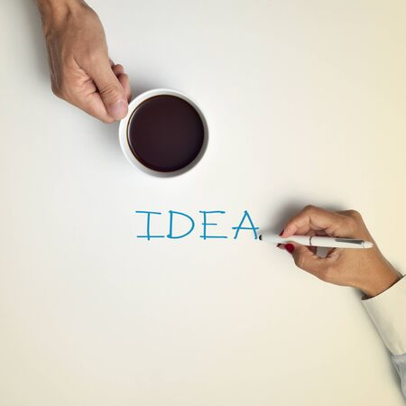 business development: high-angle shot of a young man with a cup of coffee and a young woman writing the word idea with a pen