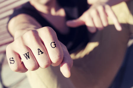 swag: closeup of a young man showing his fist with the word swag tattooed in his knuckles, with a filter effect