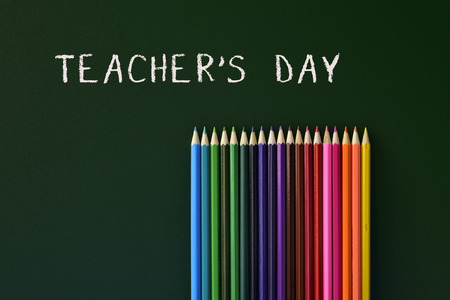 secondary school: some coloured pencils of different colors and the text teachers day written in a green chalkboard
