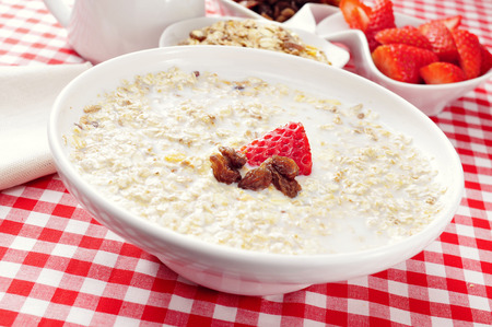 sultana: closeup of a bowl with porridge with sultana raisins and strawberry, on a set table with a checkered tablecloth for breakfast Stock Photo