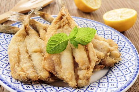 fried: closeup of a plate with spanish boquerones fritos, battered and fried anchovies typical in Spain, on a rustic wooden table