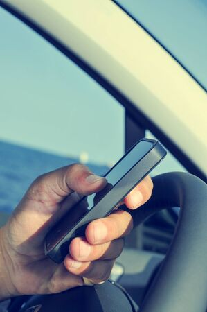 travelling salesman: closeup of a man using a smartphone while driving a car