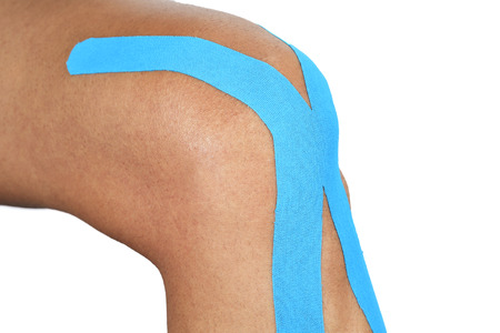 tapes: closeup of a young man with a blue elastic therapeutic tape in his knee, on a white background Stock Photo