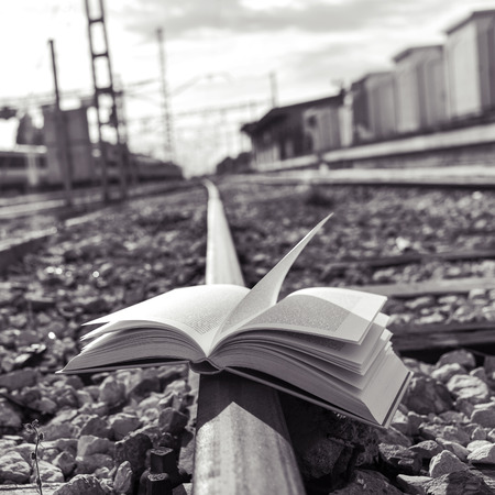 black and white railroad tracks: closeup of an open book on the railroad tracks, in black and white Stock Photo