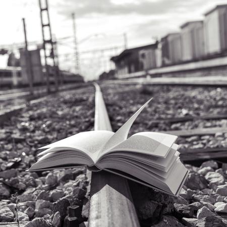ferrocarril: primer plano de un libro abierto sobre las vías del ferrocarril, en blanco y negro