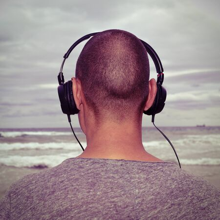 generation y: closeup of a young man seen from behind listening to music with headphones in front of the sea, with a filter effect