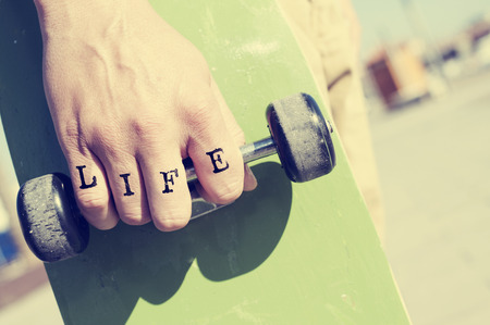 knuckles: closeup of a young man with the word life tattooed in his knuckles holding a skateboard