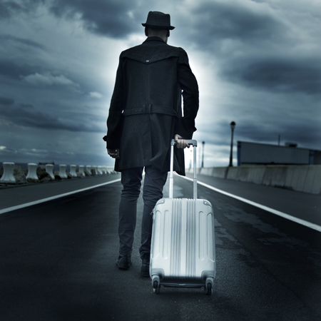 seeker: closeup of a young man seen from behind carrying his rolling suitcase, with a dramatic effect Stock Photo