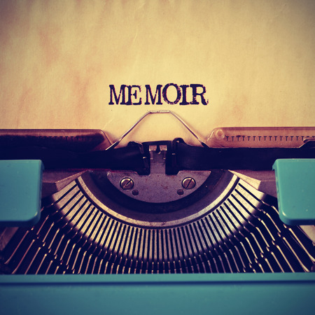 memoir: closeup of a blue retro typewriter and the word memoir written with it in a yellowish foil