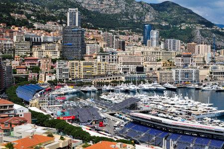 monegasque: La Condamine, Monaco - May 16, 2015: Aerial view of the Port Hercules in La Condamine, Monaco, during the preparations for the 73 Monaco Grand Prix, and Monte Carlo in the background