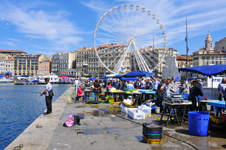 city fish market: Marseille, France - May 17, 2015: Sunday ambiance at the Old Port in Marseille, France. It is a busy port, used as a marina and as a terminal for boat trips, and hosts a fish market