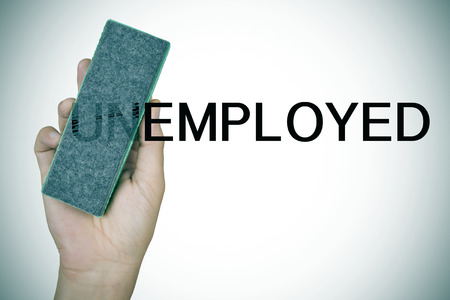 deleting: closeup of the hand of a young man deleting the prefix UN in the word unemployed with an eraser to convert it in the word employed