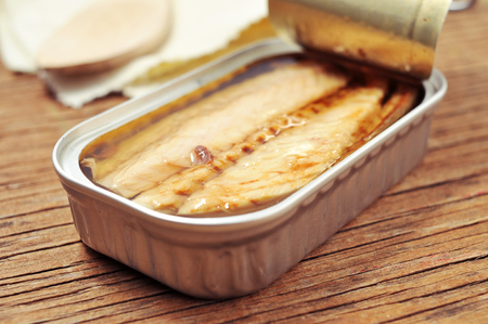 gastronomy: closeup of an open can of canned mackerel on a rustic wooden table