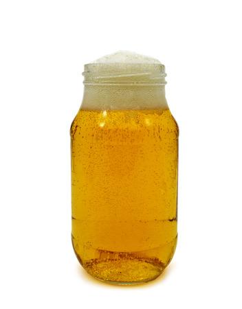 jarra de cerveza: refrescante cerveza servida en un frasco de vidrio sobre un fondo blanco Foto de archivo