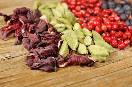 peppertree: a pile of dried hibiscus flowers, green cardamom, pink peppercorns and juniper berries on a rustic wooden table Stock Photo