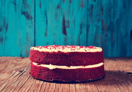 красный бархатный торт на деревенский деревянный стол и синем фоне деревянный, с эффектом фильтра Фото со стока