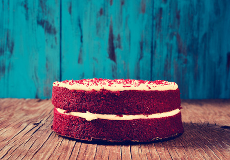 velvet: a red velvet cake on a rustic wooden table and a blue wooden background, with a filter effect Stock Photo