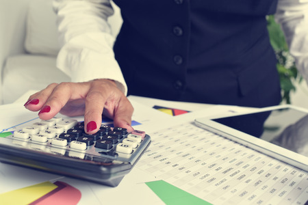 a businesswoman using an electronic calculator in her office, with a desk full of charts and a sheet of accounts Stock Photo - 45916027