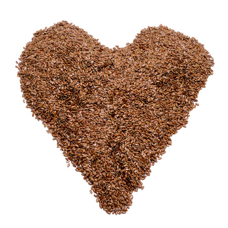 linum usitatissimum: a pile of brown flax seeds forming a heart on a white background Stock Photo