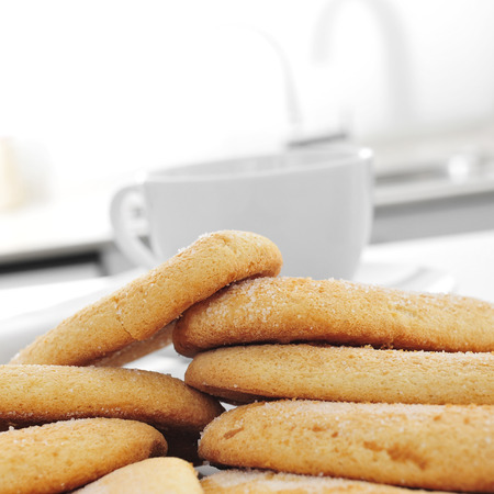 decaffeinated: closeup of some ladyfingers and a cup of coffee or tea on the kitchen table