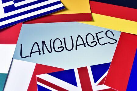 idiomas: la palabra lenguas en la pantalla de un ordenador tableta rodeado de banderas de diferentes países Foto de archivo